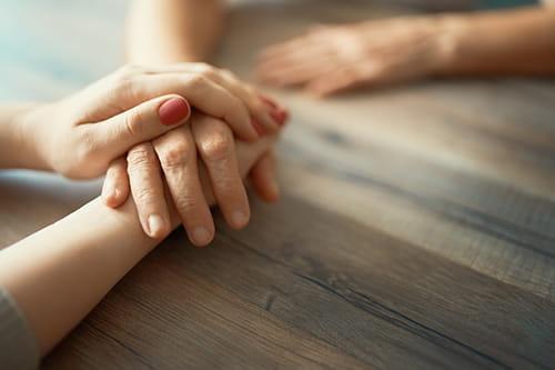 La main d'une personne posée sur celle de son amie