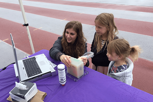 Jessica, Scientist, looking at a computer with two young children