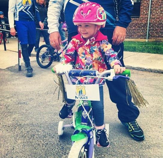Maci sitting on a bike