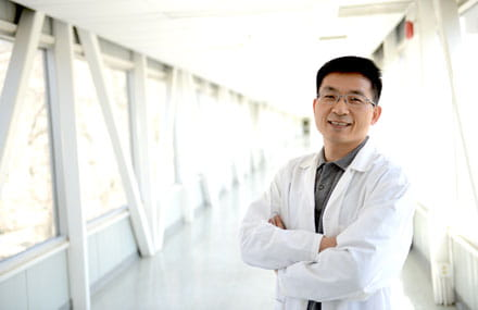 Dr. Shawn Li stands with his arms crossed in a hallway