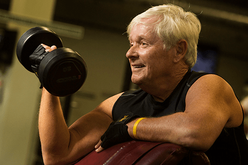 Jack smiling while lifting a weight at the gym