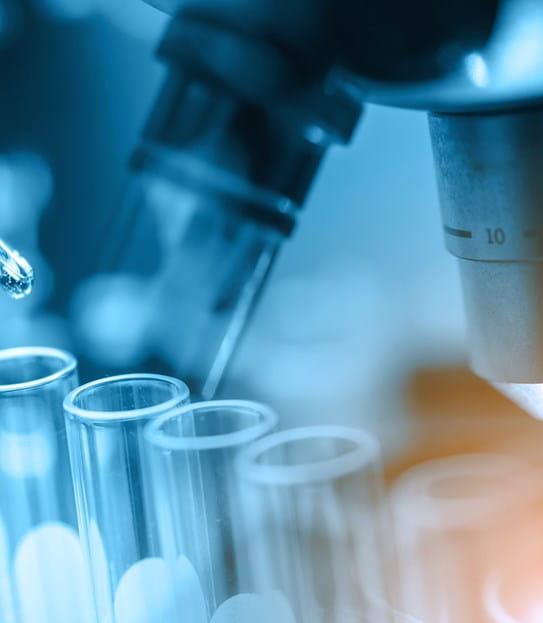Remplissage d'éprouvettes près d'un microscope dans un laboratoire