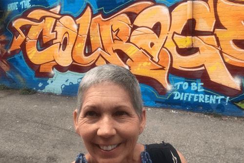 Kim devant un mur marqué de graffitis