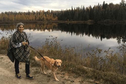 Kim walking her dog by a lake