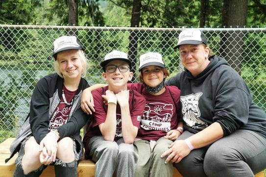 Three campers sitting on the left of their mom. They're all smiling wearing Camp Goodtimes t-shirts and hats.