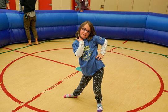 Une petite fille debout sur un terrain de basket-ball, posant, la main sur la hanche.