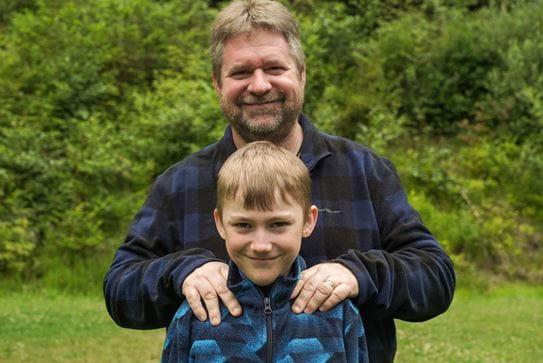 Un petit garçon souriant à la caméra. Son père, debout derrière lui, souriant, les mains sur ses épaules.