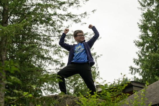 A little boy standing on a rock with his hands in the air triumphantly.