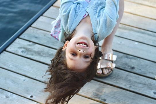 A little girl laughing while being held upside down by an adult.