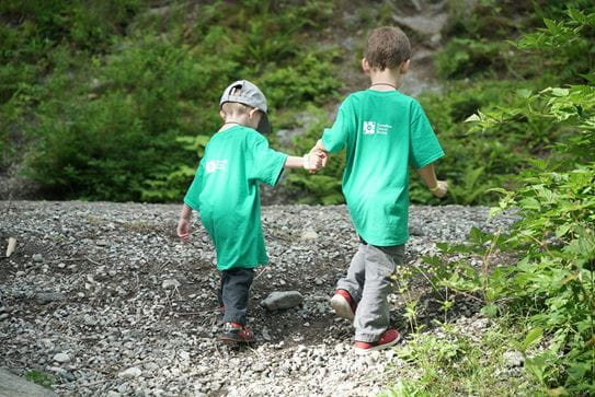 Deux petits garçons portant les tshirts verts de la Société canadienne du cancer, se tenant par la main et marchant dans la nature.