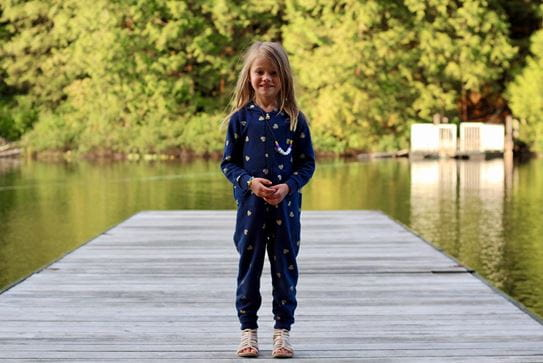 A little girl in a onesie smiling and standing on a dock at a lake.