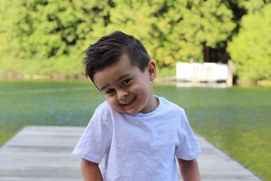 A little boy smiling on a dock at a lake.