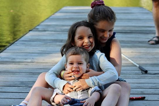 Three siblings sitting in a row hugging each other and smiling.