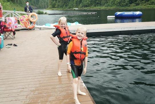 Un frère et une sœur, portant un gilet de sauvetage, debout sur le côté du quai et souriant.