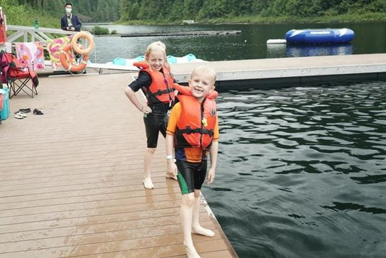 Two smiling siblings wearing lifejackets and standing on the side of a dock.