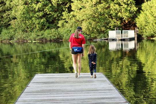 A camper and staff member walking along a dock towards a lake.