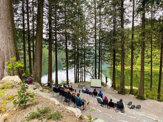 Les familles regardent un film dans la forêt, grâce à un projecteur installé à l'extérieur.