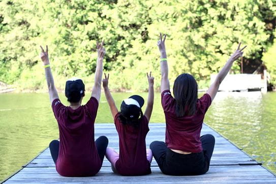 Three campers with their backs to the camera sitting on a dock. Their arms are up and they're making peace signs.