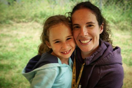 Une femme et une fillette souriant, côte à côte.