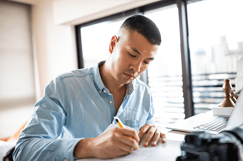 Un homme assise à un bureau écrit dans un cahier de notes.