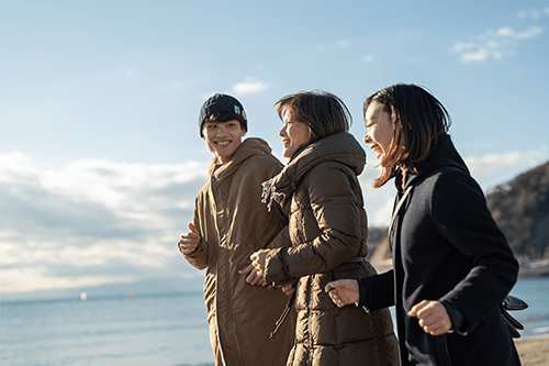A grandmother, mother and son jogging on the beach in winter.