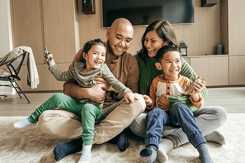 Une mère et un père qui rigolent en compagnie de leurs deux enfants.