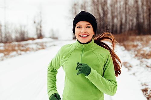 Une femme court à l'extérieur sur un chemin enneigé