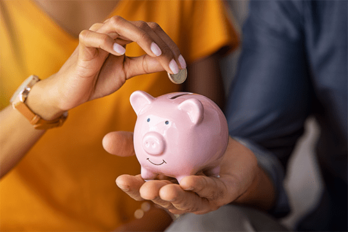 A woman and man putting a coin in a piggy bank