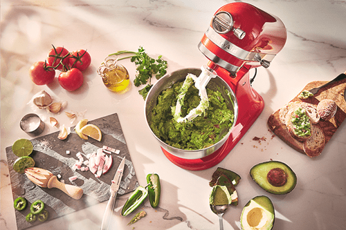 A stand mixer with guacamole in a bowl