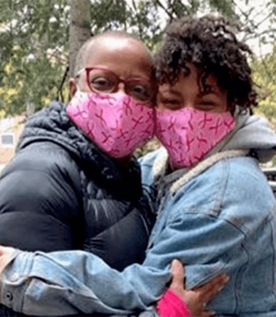 Coral tient dans ses bras sa fille, adulte, et elles portent toutes deux des couvres-visages réutilisables roses.