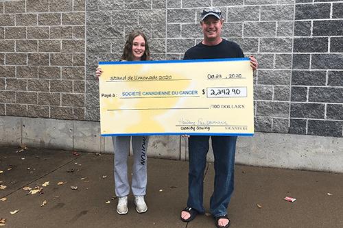 Cassidy et son père, souriants, tiennent un chèque indiquant le montant en dollars amassé grâce à son stand de limonade.