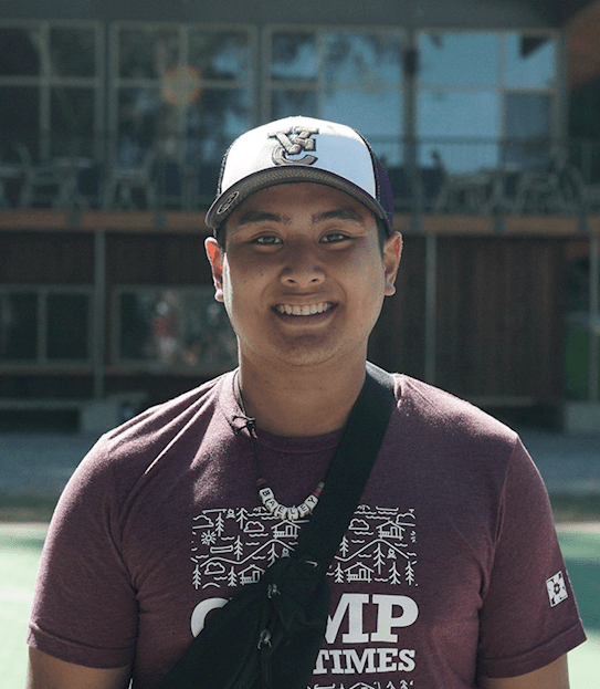 A young man smiling outside.
