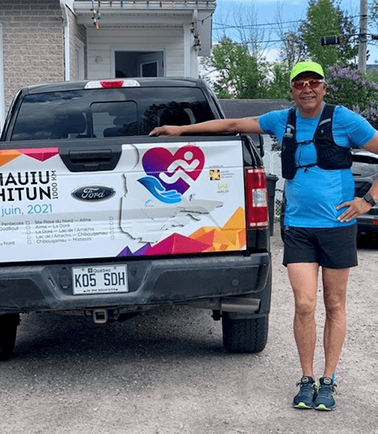 A man in a running outfit standing outside beside a truck.
