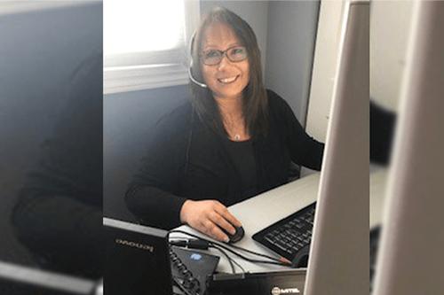 Une femme portant un casque d'écoute travaillant à un bureau et souriant à la caméra
