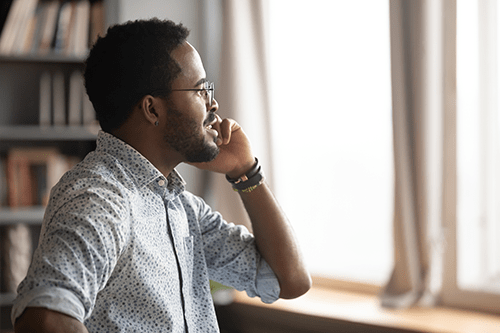 A man talking on the phone while looking out the window.