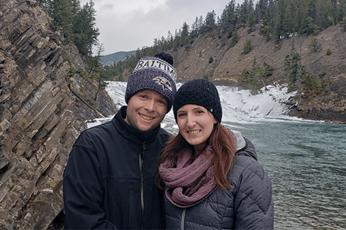A man and woman standing in front of a river smiling.