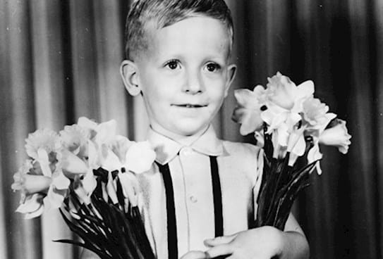 A child holding daffodils