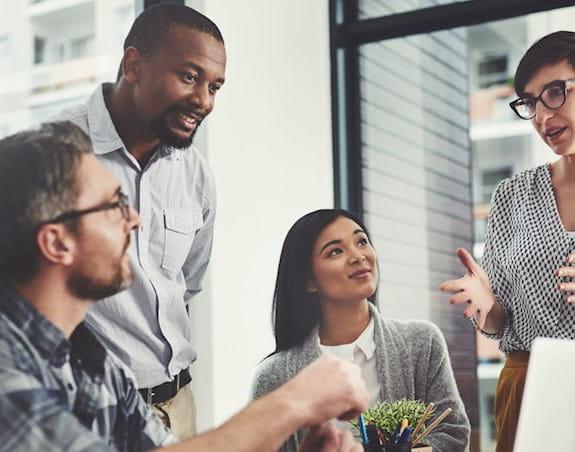 Quatre personnes discutant de leur travail dans un bureau.