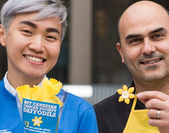 Two volunteers holding daffodils and a daffodil pin