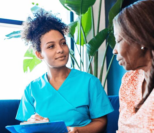 Une professionnelle de la santé écrivant sur une planchette, près d'une patiente dans la salle d'attente d'une clinique