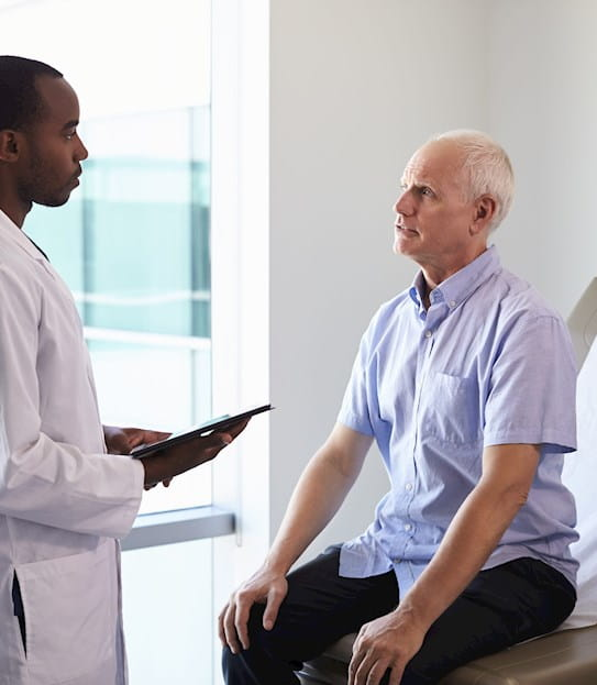 A doctor meeting with a patient in an exam room