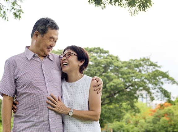 Couple smiling as they embrace while walking in a park