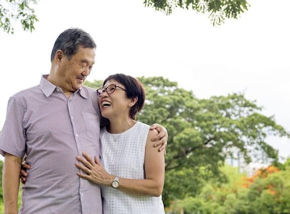 Couple qui s'enlace en souriant tout en marchant dans un parc
