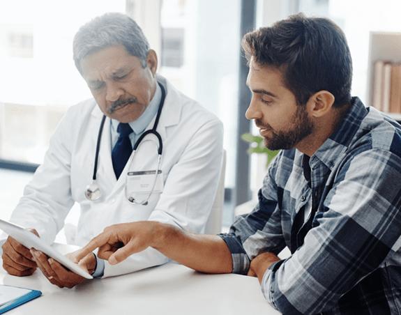 Un patient qui passe en revue une liste de questions avec son médecin