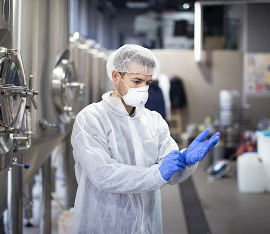 A man is standing in an industrial workplace putting on personal protective equipment