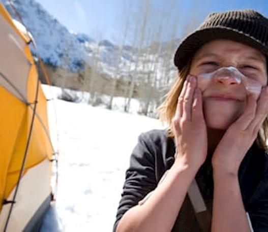 Un enfant sur un site de camping d'hiver, en train d'appliquer un écran solaire