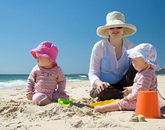 Parent with two babies on a beach