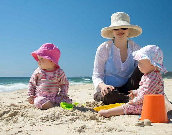 Un parent avec deux bébés sur une plage