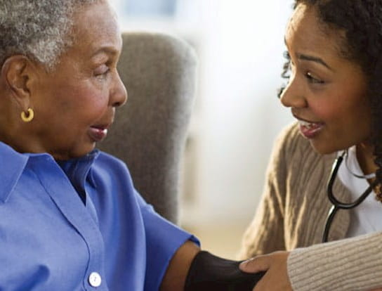 A healthcare worker taking a woman's blood pressure