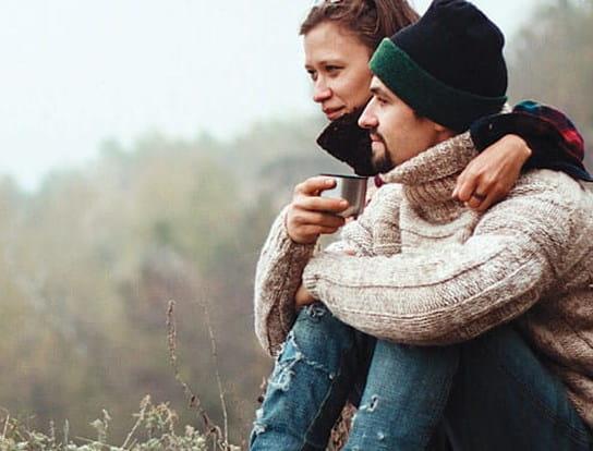 Un homme et une femme, portant des vêtements chauds, assis dans une forêt